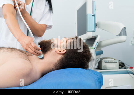 Male patient undergoing ultrasound of thyroid from female doctor in hospital - Stock Photo