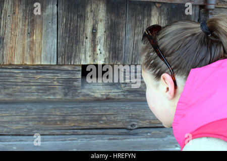 Woman Looking Through A Hole In A Brick Wall Stock Photo