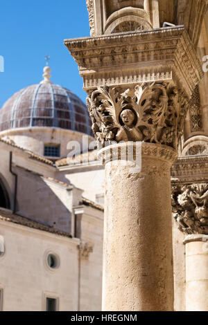 Carved ornate column of Rectors Palace and the Cathedral of the Assumption of the Virgin Mary, Dubrovnik, Croatia - Stock Photo