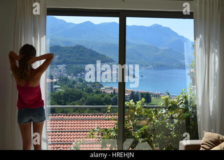 Beautiful view from the room on the coast with a girl looking through the window in Becici Budva Montenegro - Stock Photo