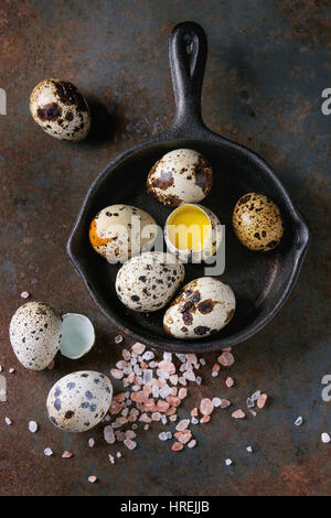Whole and broken quail eggs with yolk in shell and pink sea salt crystal in small iron cast pan over old rusty texture - Stock Photo