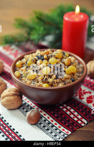 Traditional Christmas slavic dish kutia in ceramic bowl with spoon and candle - Stock Photo