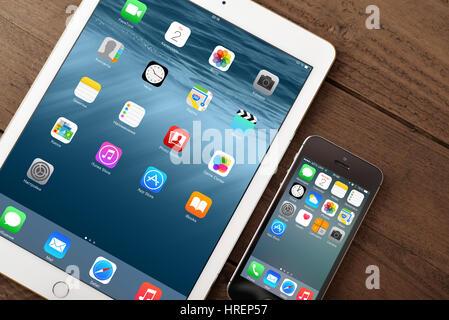 KIEV, UKRAINE - JANUARY 29, 2015: Apple iPhone 5s, iPad Air 2 on table. Apple Inc. is an American multinational - Stock Photo