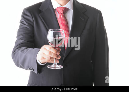 Businessman holding a glass of red wine - Stock Photo