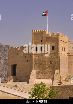 FUJAIRAH, UNITED ARAB EMIRATES - UAE flag flying over 360-year-old Fujairah Fort. - Stock Photo