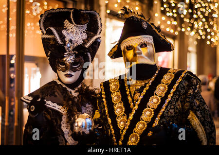 Stunning Masks from the Venice Carnival. Couple dressed up in costumes. The man wearing a gilded bauta mask. - Stock Photo