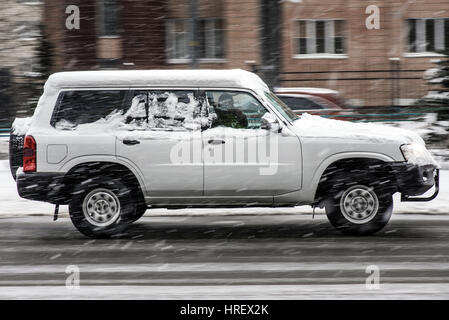 White car on road in motion in winter - Stock Photo