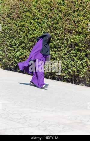 Islamic Muslim woman wearing violet black Niqab walks on Marrakesh street. Vertical shot. 15 February 2017 - Stock Photo
