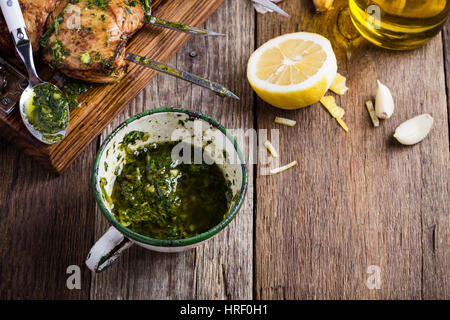 Homemade chimichurri sauce in rural white mug on rustic wooden table, traditional marinade or sauce for grilled - Stock Photo