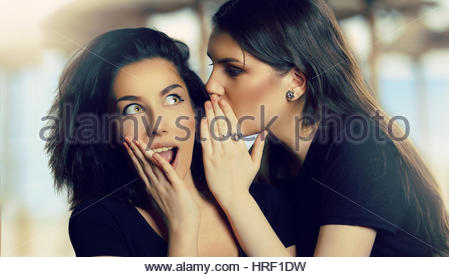 Young Teen Girl Telling a Rumor to a Friend - Stock Photo