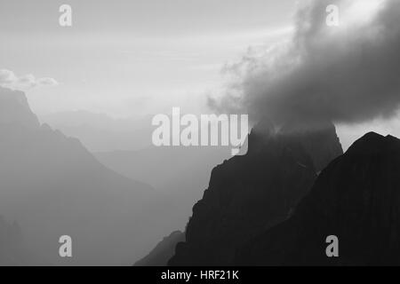 Cloud over a mountain peak. Summer evening in the Swiss Alps, view from mount Titlis. - Stock Photo