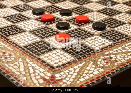 A black and white mosaic checkers table with a decorative border and red and black game pieces. - Stock Photo