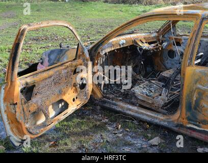 Burned out stolen car - Stock Photo