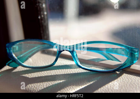 It is hard to see clearly through a dirt lens.  These aqua colored glasses sit on car dash with light coming through - Stock Photo