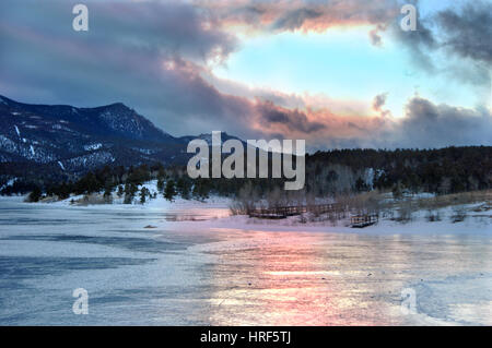 Majestic parting of the clouds during a stormy sunset filters pink and blue into a reflection on this frozen lake. - Stock Photo