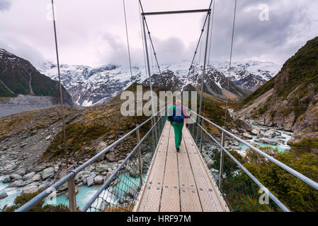 Hiker proceeds suspension bridge over River Hooker, Hooker Valley, Mount Cook National Park, Canterbury Region, - Stock Photo