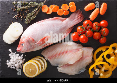 Raw fresh tilapia and vegetable ingredients, spices close-up on the table. Horizontal view from above - Stock Photo