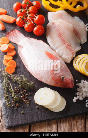 Raw fresh tilapia and vegetable ingredients, spices close-up on the table. Vertical - Stock Photo