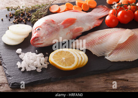 Raw fresh tilapia and vegetable ingredients, spices close-up on the table. horizontal - Stock Photo