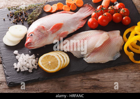 Raw whole tilapia, fillets and vegetable ingredients, spices close-up on the table. horizontal view from above - Stock Photo