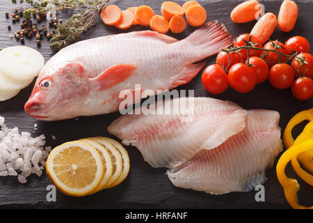 Raw tilapia and vegetable ingredients, spices close-up on the board. horizontal view from above - Stock Photo