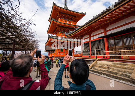 Tourists taking photos by using mobile phones in Kiyomizu dera, Buddhist Temple, in Kyoto, Janan - Stock Photo
