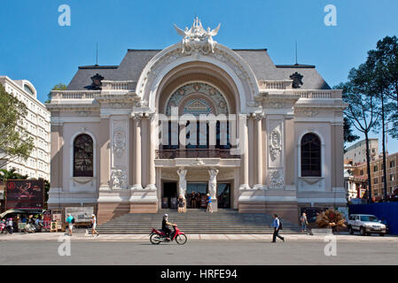 Municipal Theatre in Ho Chi Minh City with locals and tourists walking or driving past on a moped on a sunny day - Stock Photo