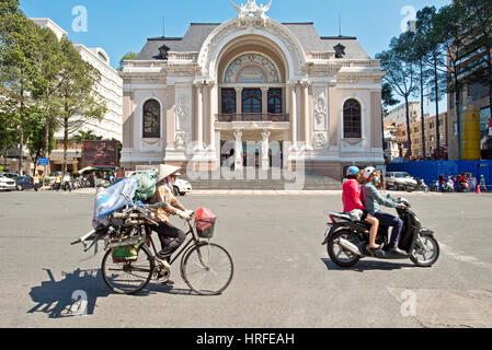 Municipal Theatre in Ho Chi Minh City with locals driving past on a moped and bicycle wearing a traditional hat - Stock Photo