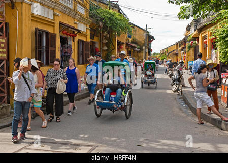 A typical street scene in Hoi An with renovated traditional colonial architecture and tourists walking around, riding - Stock Photo