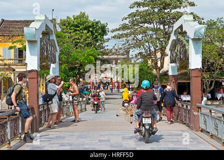 A typical street scene in Hoi An old town with tourists and local people walking, riding motor bikes across the - Stock Photo