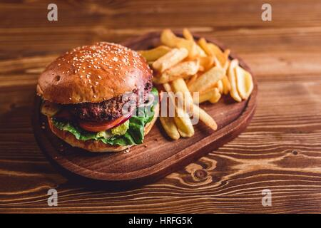 Fresh burger and french fries on wooden table. - Stock Photo
