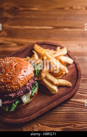 Top view on fresh burger and french fries on wooden table - Stock Photo