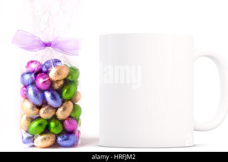 Easter coffee mug mockup next to a cellophane wrapped bag of gold wrapped chocolate mini eggs. Overlay your custom - Stock Photo