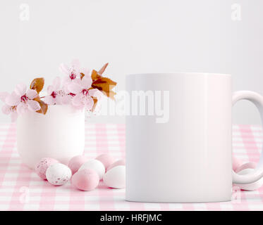Easter coffee mug mock-up, blossom in a little china vase with chocolate mini eggs.  Overlay your custom quotes - Stock Photo
