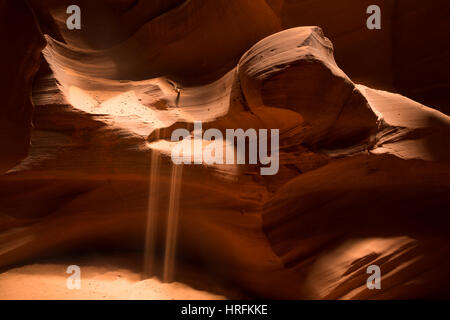 Deep inside a slot canyon in Arizona, sand placed on a shelf of rock slowly slides down and pours to the canyon - Stock Photo