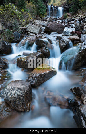 A small river or creek runs through a rocky area in Colorado. In the background a waterfall pours over a cliff, - Stock Photo