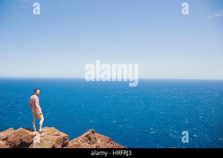 Young male traveler standing on cliff edge and looking at vast blue ocean during summer vacation on Tenerife - Stock Photo