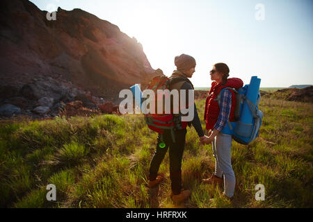 Young couple traveling with tourist backpacks: standing on top of hill holding hands and looking tenderly at each - Stock Photo