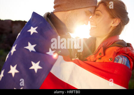 Side view portrait in bright sunlight of young happy couple standing close together and embracing tenderly wrapped - Stock Photo