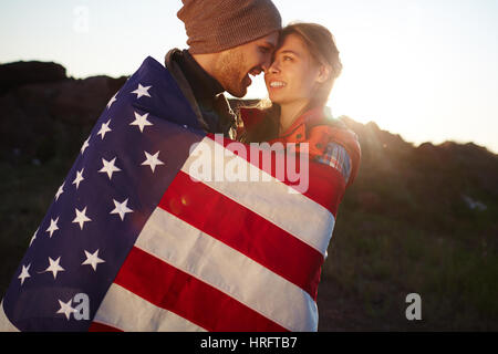 Portrait of young tourist couple standing close together in mountains, embracing tenderly wrapped in American flag - Stock Photo