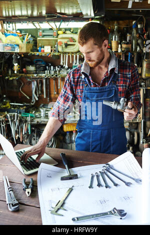 Portrait of handsome bearded mechanic wearing uniform overalls busy working in garage, assembling parts using tools - Stock Photo