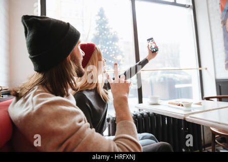View from back of couple making selfie by the table in cafe. Man showing peace sign - Stock Photo