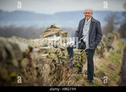 Hemingway Partnership owner Wayne Hemingway resting on a dry stone wall in the rural hills around Blackburn, Lancashire, - Stock Photo