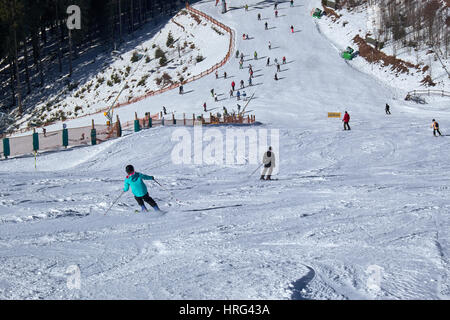 WINTERBERG, GERMANY - FEBRUARY 14, 2017: Skiers on the way down to a cross of pistes at Ski Carousel Winterberg - Stock Photo