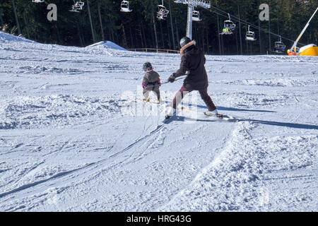 WINTERBERG, GERMANY - FEBRUARY 14, 2017: Mother and child in harness learning how to ski downhill at Ski Carousel - Stock Photo