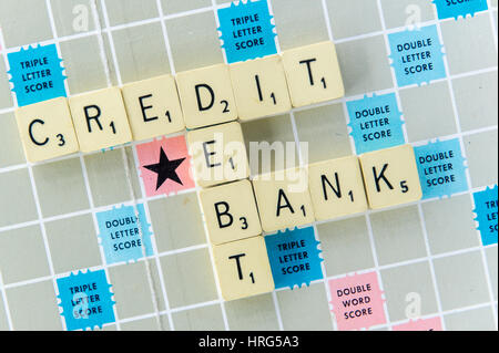 Words Credit, Debt and Bank spelt out on a Scrabble board as a financial or banking concept. - Stock Photo