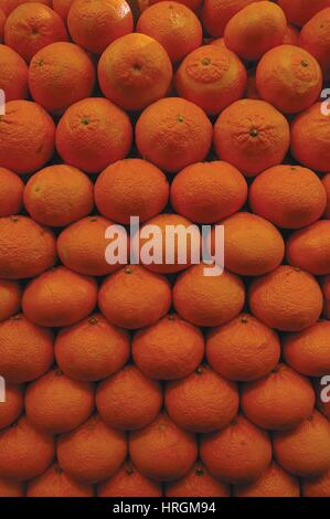 Stack of fresh oranges in farmer's market stall - Stock Photo