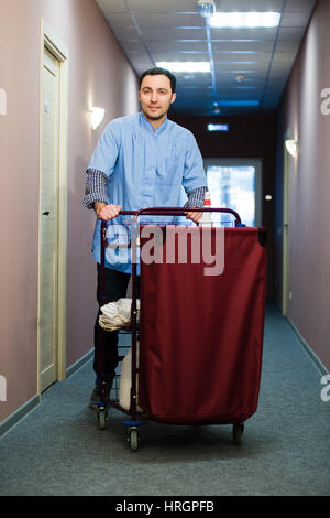 Young man pushing a housekeeping cart laden with clean towels, laundry and cleaning equipment in a hotel as he services - Stock Photo