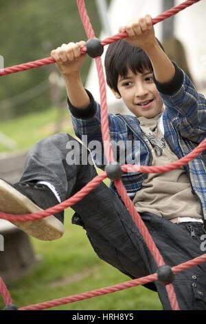 Model released, Junge am Spielplatz auf Kletterwand - boy on a playing ground - Stock Photo