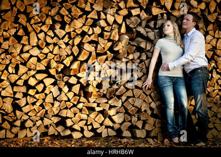 Model released, Junges Liebespaar an einen Holzstapel gelehnt - young couple leaning on a wood pile - Stock Photo